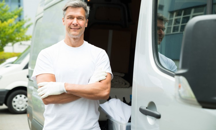 43083122 - happy male painter with arms crossed standing in front of van
