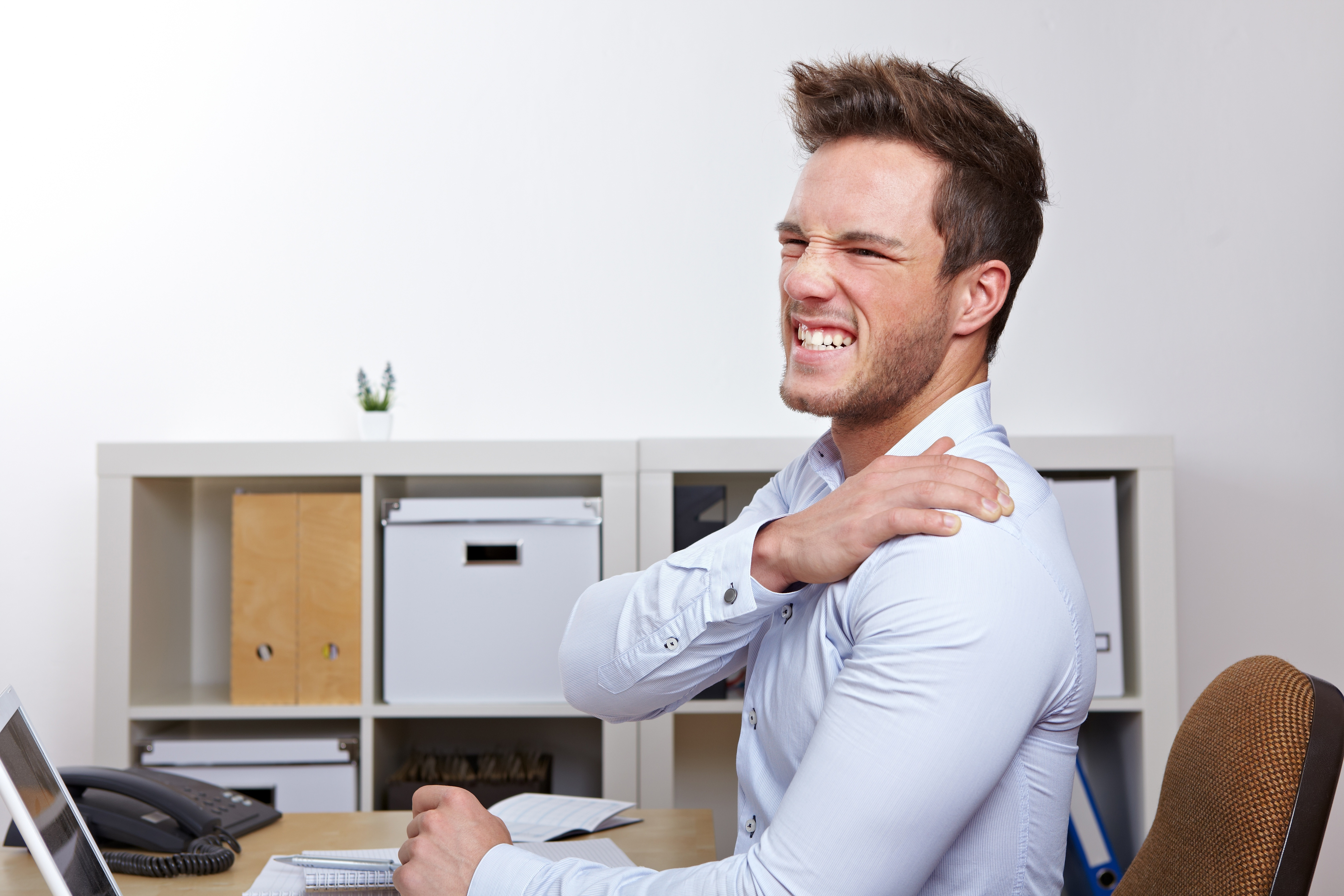 12613404 - business man with shoulder pain in office at desk
