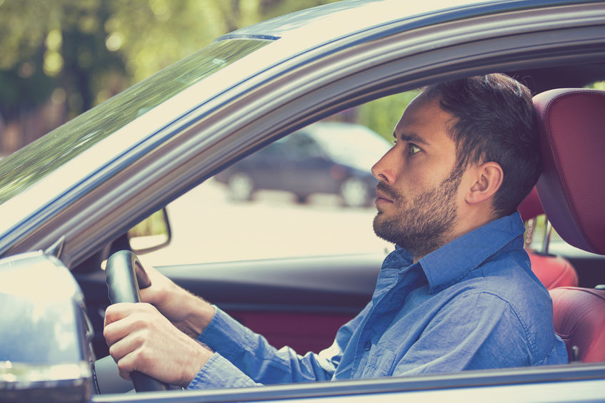 scared funny looking young man driver in the car. Inexperienced anxious motorist
