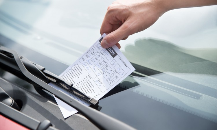 Officer's Hand Putting Parking Ticket On Car