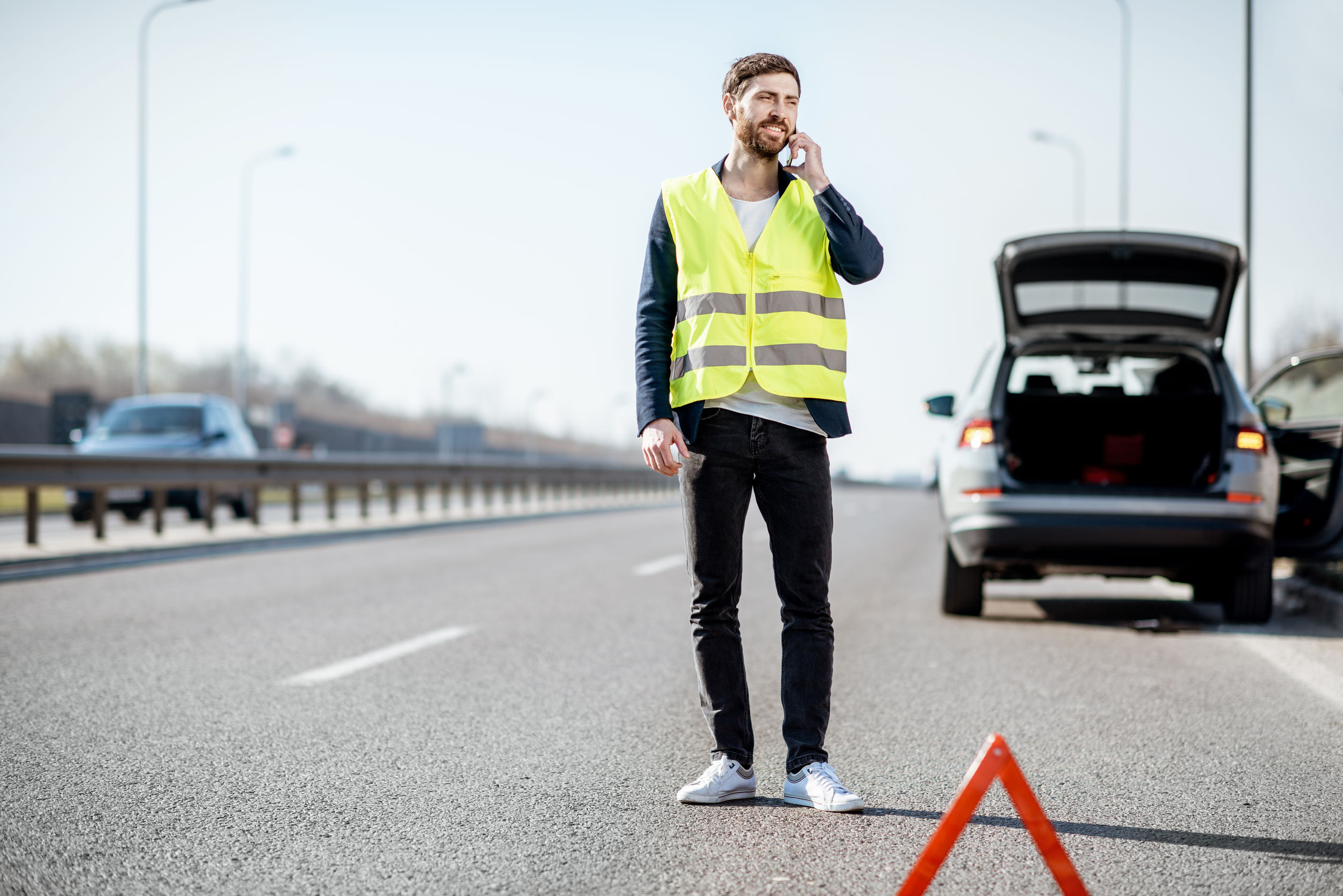 Man calling road assistance on the highway