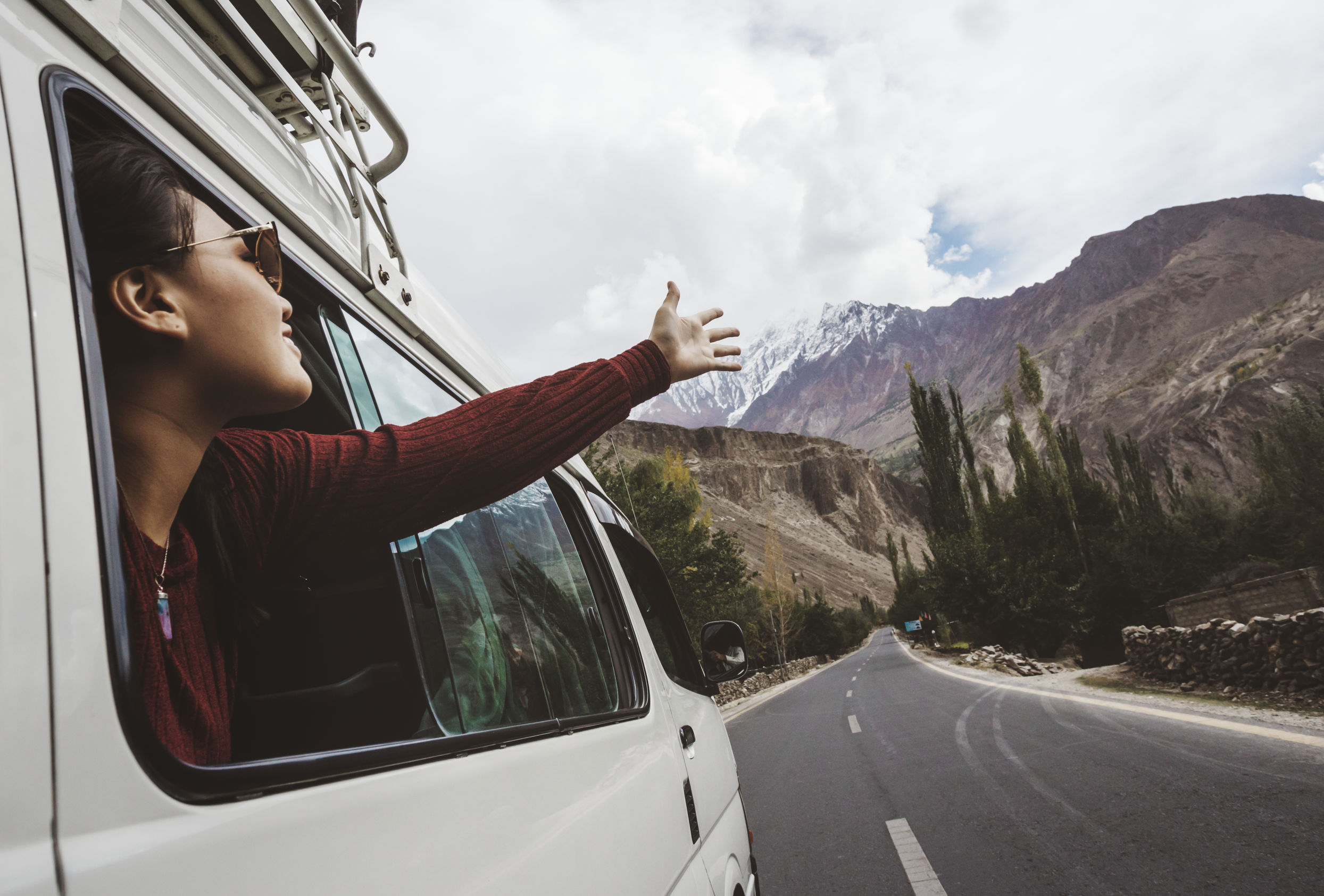 Woman enjoying the cool breeze from the car window