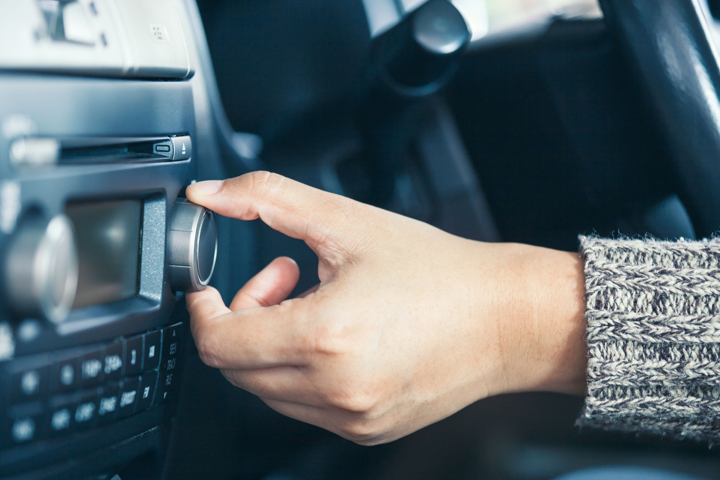 Woman hand adjusting the sound volume of car radio while driving