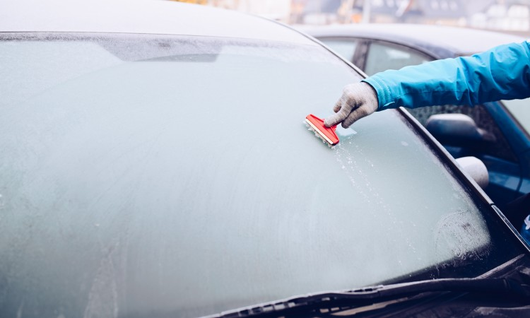 Woman removing ice from car windshield with glass scraper.