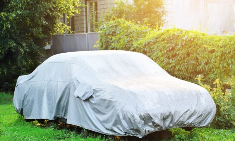 20857244 - a parked car with protective cover in wet weather