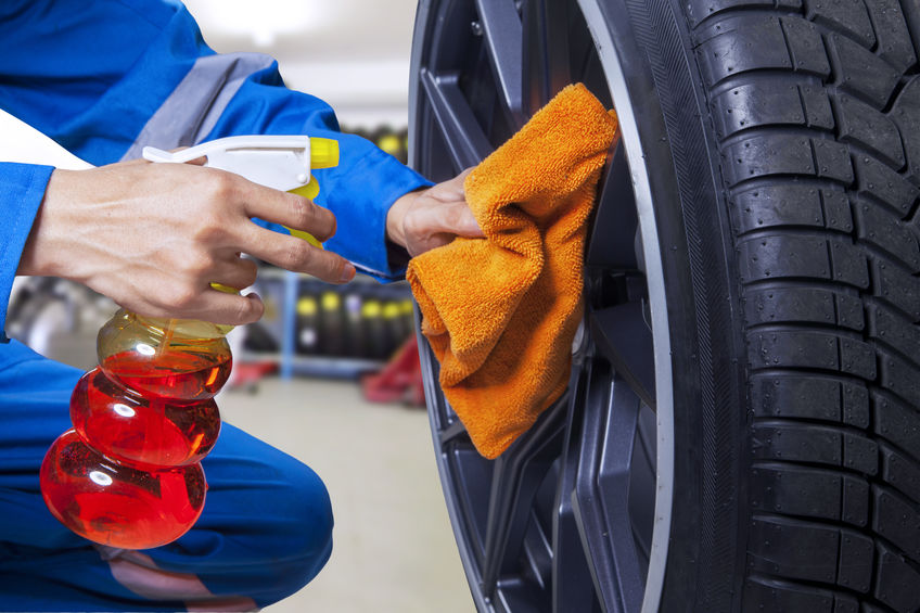 Technician cleaning a tire at workshop