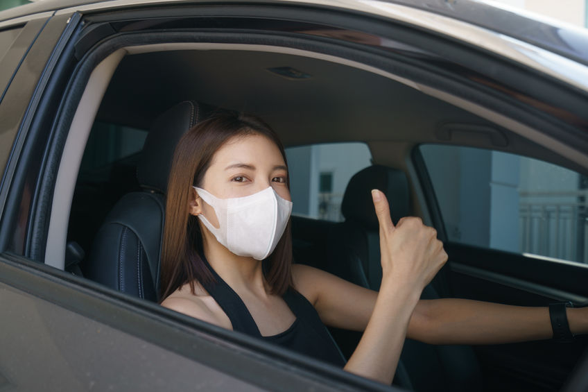 Wome wearing surgical mask in the car, for corona virus or Covid