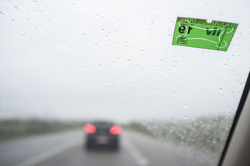 Vehicule Inspection Sticker of on windscreen a rainy day